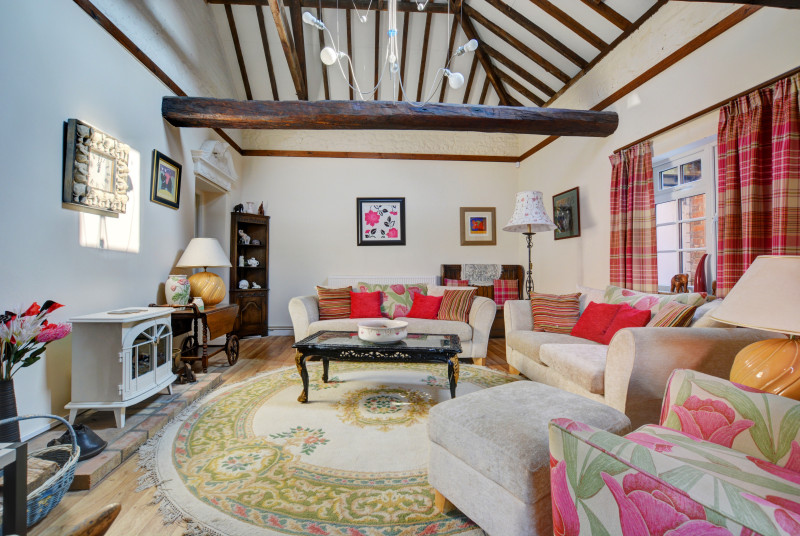 A beautiful double-height sitting room with a vaulted ceiling and original beams